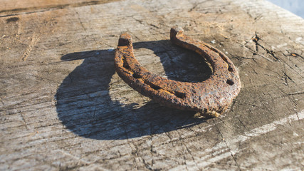 Close up of an old rusty metal horseshoe on old vintage wooden background