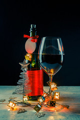 New Year's picture of bottle with red ribbon, Christmas tree toys, wine glass