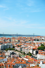 Alfama downtown and the 25 April Bridge in Lisbon, Portugal.