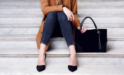 Fashion woman sit in high heels shoes hold black big bag