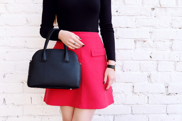 fashion outfit, red skirt and black big bag in girl hand