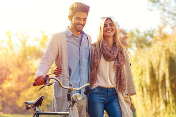 Young couple with bicycle walking in park on sunny autumn day.