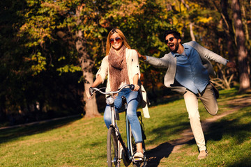 Happy young couple having fun riding a bicycle on sunny autumn day in the park.