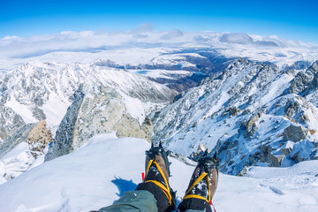 First person view to legs in crampons take a rest on the top of mountain