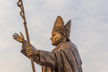 Ancient brass sculpture of Pope, the bishop of Rome with golden sunlight glare on the statue. Fotomurales