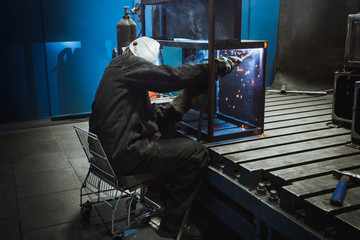 A man with a welding mask welding something together