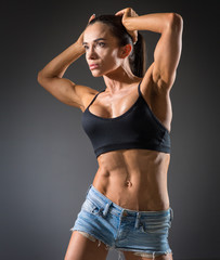 athletic young woman with muscles doing exercises with dumbbells bodybuilding in the gym