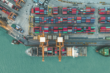Container ship in import export and business logistic, By crane, Trade Port, Shipping cargo to harbor, International transportation, Business logistics concept, Aerial view from drone.