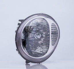 oval car headlight on white background with reflection. isolated