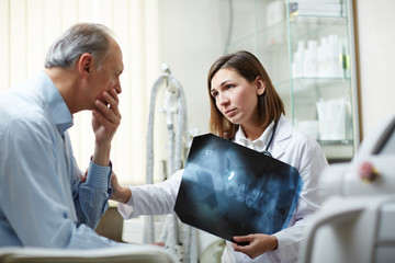 Senior patient worried by results of x-ray exam listening to his doctor advice