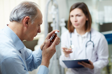 Senior patient looking at pill bottle with effective drugs