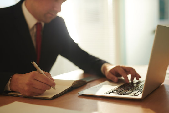 Businessman planning work and browsing in the net by workplace