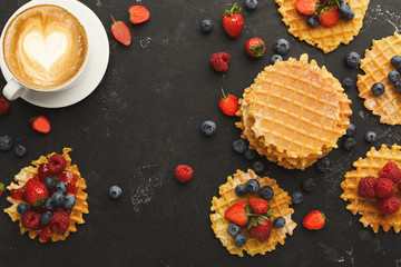 Round belgium waffles with berries, tasty breakfast on black background