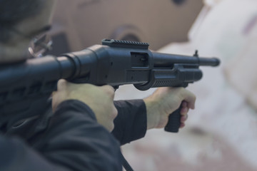 Man is aiming from a shotgun close-up. Weapons