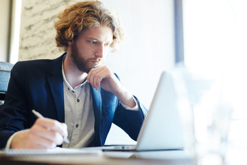 Pensive young man looking at online data in front of laptop