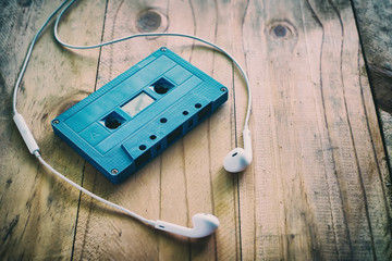 Blue retro cassette tape and white earphone on wooden table, added color filler, vintage and retro effect