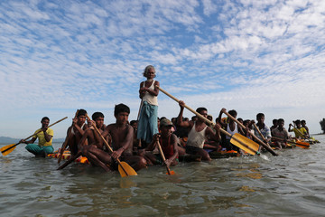 Rohingya refugees cross the Naf River on an improvised raft to reach Bangladesh, in Teknaf, Bangladesh