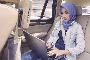 Muslim woman with laptop in car
