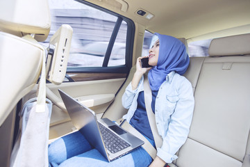 Muslim woman with laptop and cellphone in car