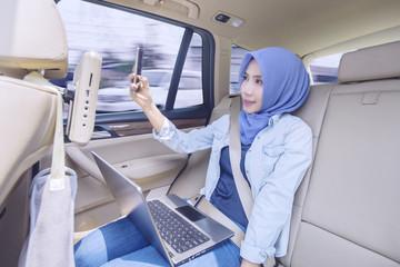 Muslim woman taking selfie photo in car