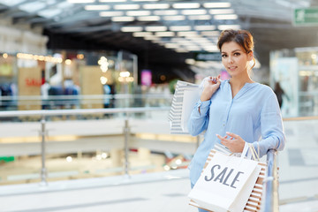 Young shopper with paperbags looking at camera after visiting holiday sale