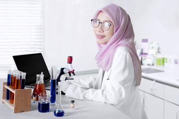 Muslim scientist smiling in the laboratory