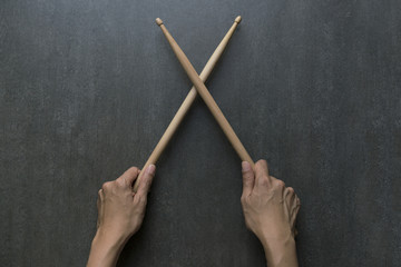 hand holding drum stick on black table background, music practice concept