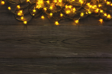 Christmas lights border on grey wooden background