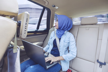 Female muslim with laptop inside car