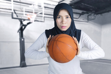 Female muslim posing with basketball