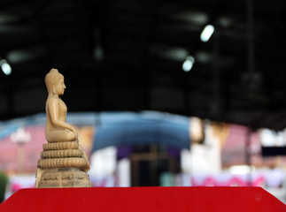 Beside of beige color resin of buddha statue. A carved Buddha figurine.