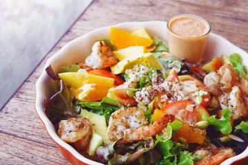 Fresh fruit salad with grilled shrimp and salad dressing served on red bowl.