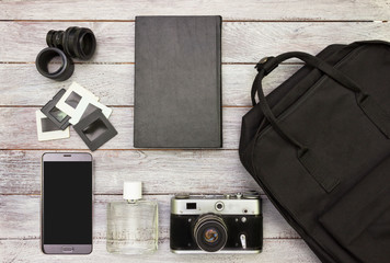 Top view accessories   -backpack, vintage camera,mobile phone,retro slides ,lens and parfume on white wooden background.Black and white colors.Traveling concept.