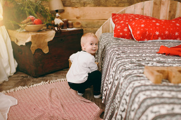 Cute little child boy dressed in black and white pajamas sitting on the floor at the bed in wooden rustic room at home. Christmas good mood. New Year. Lifestyle, family and holiday 2018 concept