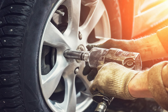 Car mechanic worker doing tire or wheel replacement with pneumatic wrench in garage of repair service station