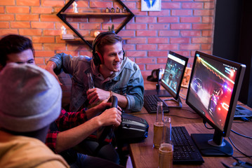 Positive young stylish gamers are resting together at home and drinking beer while playing car racing video game using steering wheel. Focus on joyful guy is sitting at table in headphones