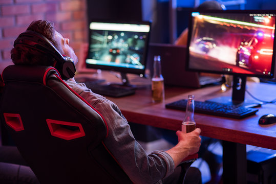 Feeling tired. Back view of relaxed young gamer in headphones is resting in chair and drinking beer while enjoying car racing video game. Selective focus