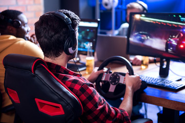 Adult entertainments. Back view of concentrated young man is sitting at desk with friends and playing car racing video game using steering wheel. Males are wearing headphones and resting in background