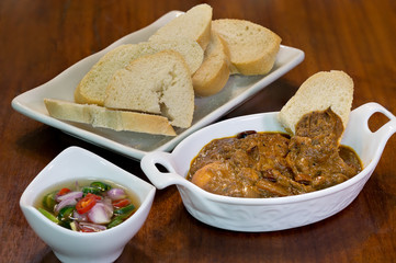 Bread eat with Chicken Massaman curry and pickles in white dish on wooden table