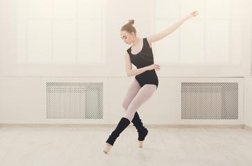 Beautiful ballerina stands in ballet assemble