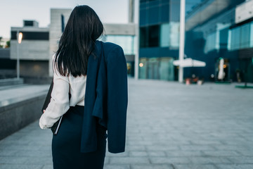 Businesswoman with suit in hand, back view