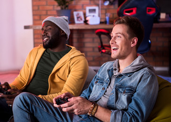 Excited players. Cheerful stylish young man is sitting on couch and using home video console. He is expressing gladness while looking at screen. Positive african guy is holding joystick in background