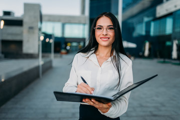 Portrait of business woman writing in notebook