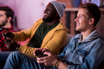 Adult party. Joyful fashionable attractive guys are enjoying play station. They are sitting on sofa and expressing gladness while holding joystick and looking at monitor. Selective focus