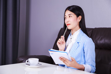 business woman sitting at the desk and thinking to her work