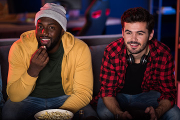 Relaxed and happy. Portrait of cheerful young stylish men are sitting on sofa in cozy apartment. They are looking at camera with joy. African guy is eating popcorn while his friend playing video games
