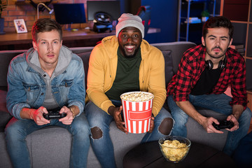 Have fun together. Portrait of pleasant stylish guys are sitting on comfortable couch and holding joystick while enjoying home video game console. African man is resting on sofa and holding popcorn
