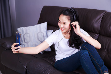 woman enjoying music in headphones, making selfie photo with cellphone while lying on sofa