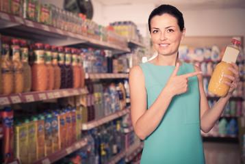 Female in the supermarket holding juice in bottle