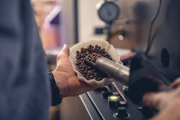 Close up male worker keeping bowl and special equipment with beans coffee. Control concept